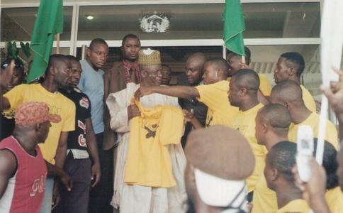 """Douala le 13 février, conférence de presse de Ni John Fru Ndi, Joseph Désiré Som 1 lui tend un t-shirt """"Non"""" contre la modification de la Constitution par Paul Biya. Photo © J.D.Som 1"""